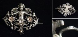 Pierced old silver brooch with putto